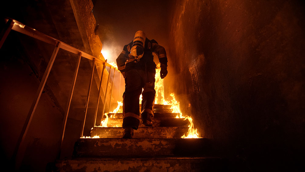 Firefighter Going Up The Stairs in Burning Building.